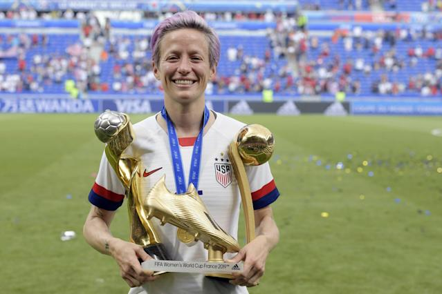 Megan Rapinoe poses with the Women's World Cup trophy, the Golden Boot and the Golden Ball. (Getty)
