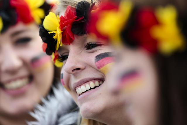 Three women arrive at the airport Tegel to welcome German national soccer team in Berlin Tuesday, July 15, 2014. Germany beat Argentina 1-0 on Sunday to win its fourth World Cup title. (AP Photo/Markus Schreiber)