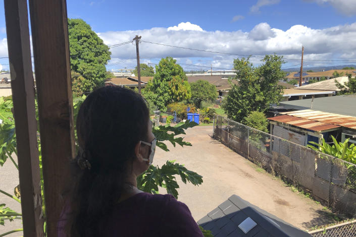 Susan Galicha looks out at a train on Honolulu's rail track in the distance from her front porch in Waipahu, Hawaii, on Oct. 30, 2020. Honolulu is building one of the nationís most expensive rail lines to address some of the nation's worst traffic but tax revenue declines during the pandemic and spiraling costs mean it doesn't currently have enough money to finish the 20-mile route as planned. (AP Photo/Audrey McAvoy)