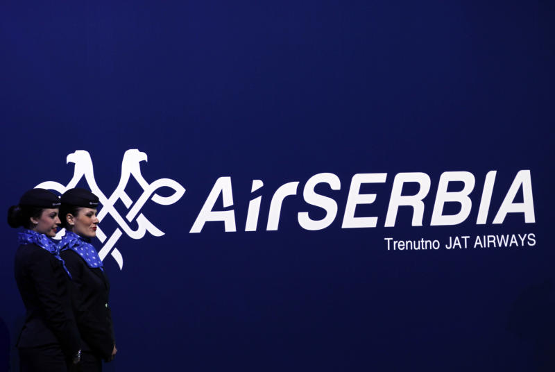"New cabin crew members stand by the Air Serbia logo during an inauguration ceremony of the first Airbus A319-100 aircraft in Air Serbia livery at Belgrade's Nikola Tesla Airport, Serbia, Friday, Oct. 25, 2013. Officials say that Air Serbia, Balkan country's new national carrier partly owned by Etihad Airways, formally starts flying this weekend, spelling the end for the old loss-making JAT Airways. Air Serbia's chief manager Dane Kondic said Friday that the company's inaugural flight will take place on Saturday to Abu Dhabi, United Arab Emirates. He says that ""it is an important flight that will mark a crossroads."" Kondic and Serbia's deputy prime minister Aleksandar Vucic unveiled at a ceremony at Belgrade's airport an Airbus A319 plane bearing a double-headed eagle logo in Serbia's national, red, white and blue colors. Vucic says Air Serbia hopes to become the leading regional airline. (AP Photo/Darko Vojinovic)"