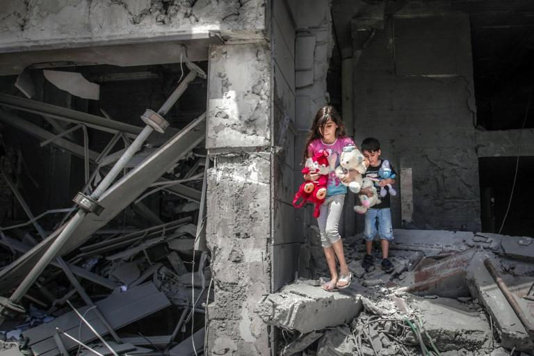 Palestinian children salvage toys from their home at the Al-Jawhara Tower in Gaza City, which was heavily damaged in Israeli airstrikes