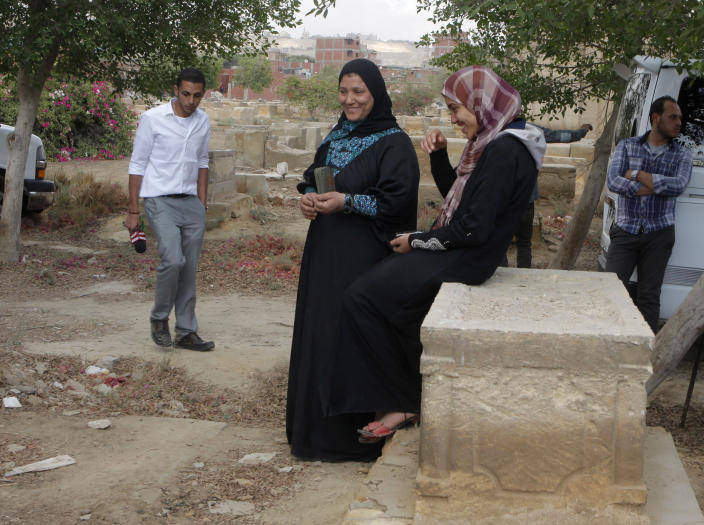 Egyptian women sit on a grave at the Jewish cemetery, in Cairo, Egypt, Thursday, April 18, 2013. The leader of Egypt's dwindling and aging Jewish community, known for her tireless work preserving synagogues and a once-sprawling Jewish cemetery, died Saturday at the age of 82. Carmen Weinstein was buried Thursday in the Bassatine cemetery she herself worked to save since 1978. It is the only Jewish cemetery left in Cairo and is the largest in Egypt. The transformation of Bassatine mirrors the dramatic changes Egypt has undergone as its population skyrocketed and poverty grew. Parts of Bassatine were turned into a garbage dump, while another area was seized by antiquities' officials. Weinstein was able to preserve a small area as a Jewish cemetery. (AP Photo/Amr Nabil)