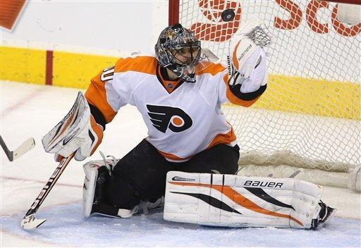 Philadelphia Flyers goaltender Ilya Bryzgalov juggles a puck shot by Winnipeg Jets' Nik Antropov (80) on a breakaway attempt during the second period of an NHL hockey game in Winnipeg, Manitoba, Tuesday, Feb. 12, 2013. (AP Photo/The Canadian Press, Trevor Hagan)