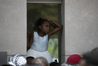 A girl sits on an outer window ledge of the U.S. Embassy in Port-au-Prince, Haiti, Friday, July 9, 2021. A large crowd gathered outside the embassy amid rumors on radio and social media that the U.S. will be handing out exile and humanitarian visas, two days after Haitian President Jovenel Moïse was assassinated in his home. (AP Photo/Fernando Llano)