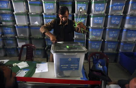 An Afghan election worker opens the lock to a ballot box to start counting ballot papers for an audit of the presidential run-off in Kabul