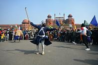 A Nihang or a Sikh warrior performs in front of Red Fort as farmers protest