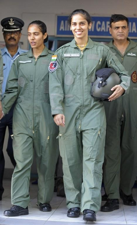 Indian badminton player Saina Nehwal (C), clad in a flight suit, walks with Indian Air Force personnel before her flight on a Kiran MK-1 trainer aircraft at Air Force Academy Dundigal, in the outskirts of Hyderabad, on September 28, 2012. Nehwal, who flew on an Air Force trainer aircraft, was a special guest at the academy for the closing ceremony of the Inter Squadron Sports championship. AFP PHOTO / Noah SEELAM