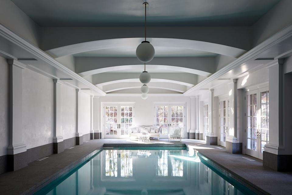 "<div class=""caption""> Story opted for a neutral aesthetic throughout the home, including in the indoor pool area, where pendants from <a href=""https://www.alliedmaker.com/"" rel=""nofollow noopener"" target=""_blank"" data-ylk=""slk:Allied Maker"" class=""link rapid-noclick-resp"">Allied Maker</a> and a contrasting gray stripe against the white walls keep the vibe light and bright. </div>"
