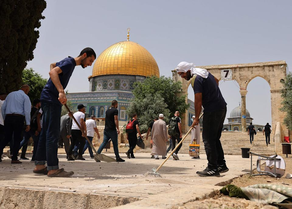 Palestinians clean the Al-Aqsa mosque compound on May 10, 2021, following renewed violence with Israeli police.