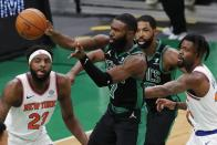 Boston Celtics' Jaylen Brown (7) passes off against New York Knicks' Mitchell Robinson (23) and Reggie Bullock, right, during the first half of an NBA basketball game, Sunday, Jan. 17, 2021, in Boston. (AP Photo/Michael Dwyer)