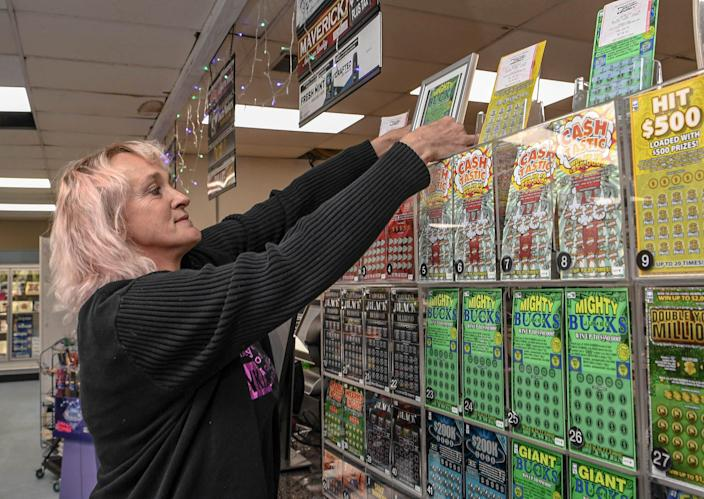 Aggi Tarnowski looks at a copy of a winning lottery scratch-off ticket sold at the KP Food Mart in Anderson, South Carolina. The $350,000 win with a scratch off also meant the store got $3,500, which Tarnowski said the store would put into having Thanksgiving meals to go for the community the store is in. Locals also donated food for the Thanksgiving meals, which the store owners say they will match.