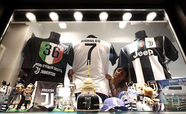A picture taken on July 11, 2018 shows a saleswoman making the shop window with a Cristiano Ronaldo Juventus jersey in a shop in Turin. (Getty Images)