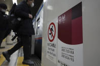 People wearing protective masks to help curb the spread of the coronavirus get on a subway with a banner of Tokyo 2020 Olympic and Paralympic games in Tokyo Thursday, Jan. 14, 2021. The Japanese capital confirmed more than 1500 new coronavirus cases on Thursday. (AP Photo/Eugene Hoshiko)