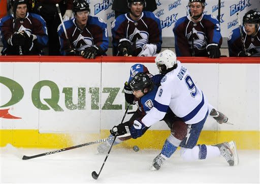 Colorado Avalanche center Ryan O'Reilly, left, fights for control of the puck with Tampa Bay Lightning right wing Steve Downie, right, in the second period of an NHL hockey game on Friday, Dec. 23, 2011, in Denver. (AP Photo/Chris Schneider)