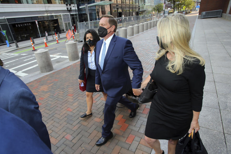 John Wilson, center, holds his wife's hand, right, as he leaves the John Joseph Moakley Federal Courthouse after the first day of his trial in the college admissions scandal, Monday, Sept. 13, 2021, in Boston. (AP Photo/Stew Milne)
