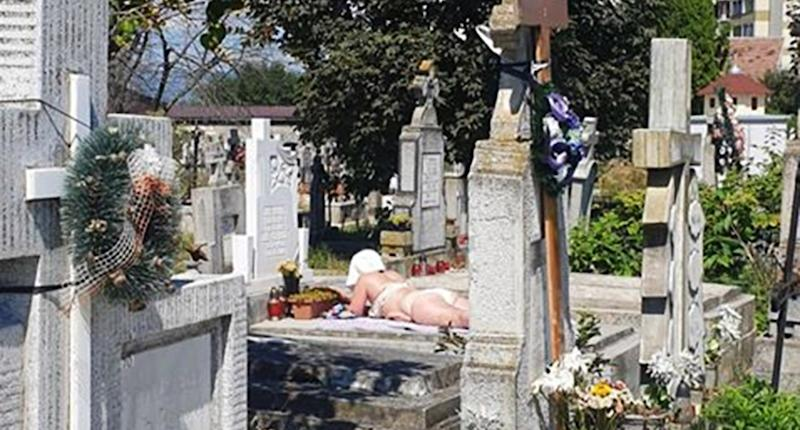 A woman was pictured sunbathing on a grave at a cemetery.
