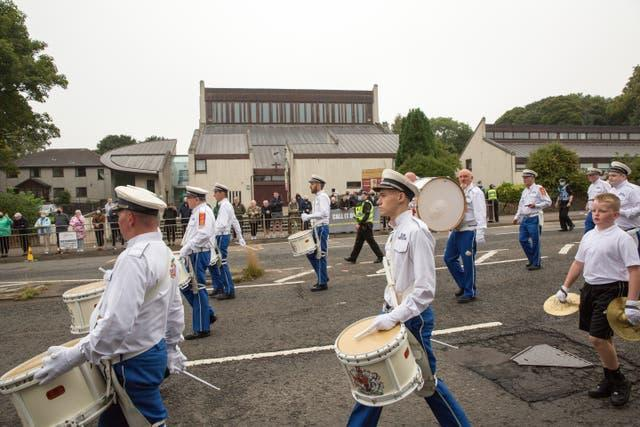 A silent Orange Order band passes by