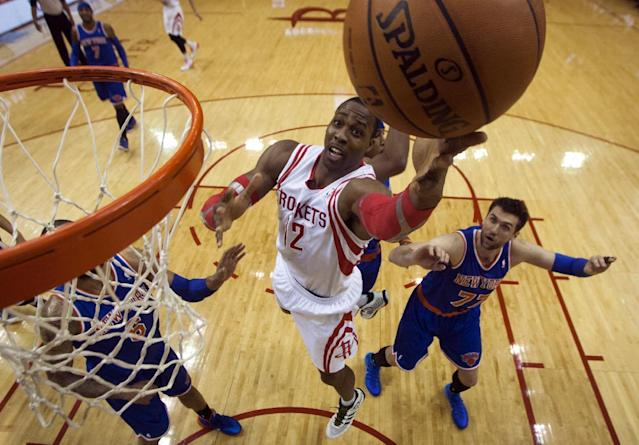 Houston Rockets center Dwight Howard (12) lays the ball up during the first period of an NBA basketball game against the New York Knicks, Friday, Jan. 3, 2014, in Houston. (AP Photo/Patric Schneider)
