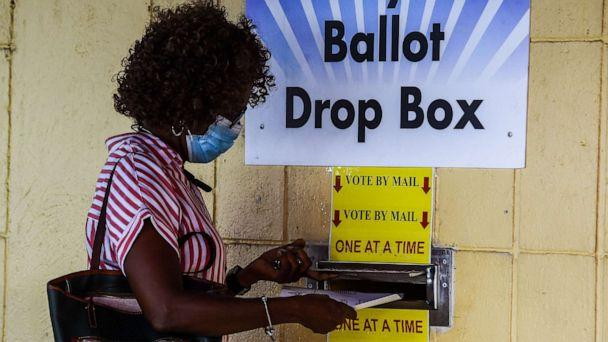 PHOTO: A woman drops her ballot by mail at Broward County Supervisor Of Elections Office in Lauderhill, Fla., Oct. 5, 2020. (Chandan Khanna/AFP via Getty Images)