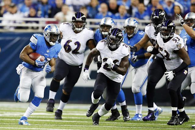 Detroit Lions running back Reggie Bush, left, pulls away from the Baltimore Ravens defense during the first quarter of an NFL football game in Detroit, Monday, Dec. 16, 2013. (AP Photo/Rick Osentoski)