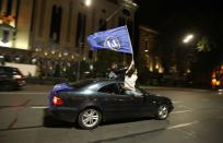 Supporters of the ruling Georgian Dream party wave a flag from a car after exit polls were announced during parliamentary election, in Tbilisi