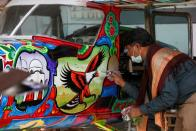 Painter Haider Ali paints Pakistani truck art on a two-seater Cessna aircraft at Jinnah International Airport in Karachi