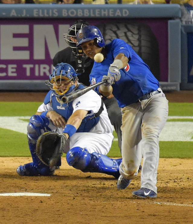 Chicago Cubs' Starlin Castro, right, hits a double as Los Angeles Dodgers catcher A.J. Ellis catches during the sixth inning of a baseball game, Friday, Aug. 1, 2014, in Los Angeles. (AP Photo/Mark J. Terrill)