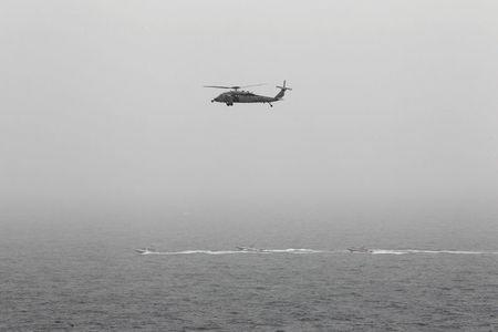 Three Iranian Revolutionary Guard boats are seen near the U.S. aircraft carrier, USS George H. W. Bush while transiting Straits of Hormuz as U.S. Navy helicopter hovers over them