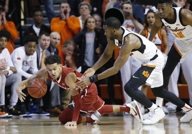 Oklahoma guard Trae Young left, keeps the ball from Oklahoma State guard Tavarius Shine, center, in the first half of an NCAA college basketball game in Stillwater, Okla., Saturday, Jan. 20, 2018. (AP Photo/Sue Ogrocki)