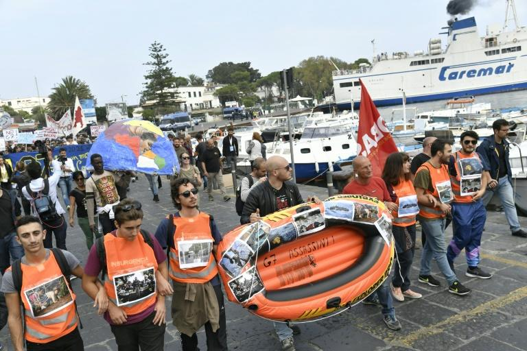 Protesters at G7 ministers meeting carry a rubber boat as they arrive on the Italian island of Ischia, to symbolize migrants who died at sea trying to cross the Mediterranean