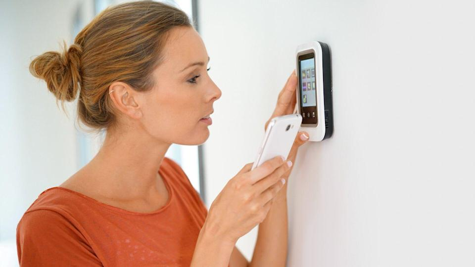 Woman using smartphone to control home connectivity interface.