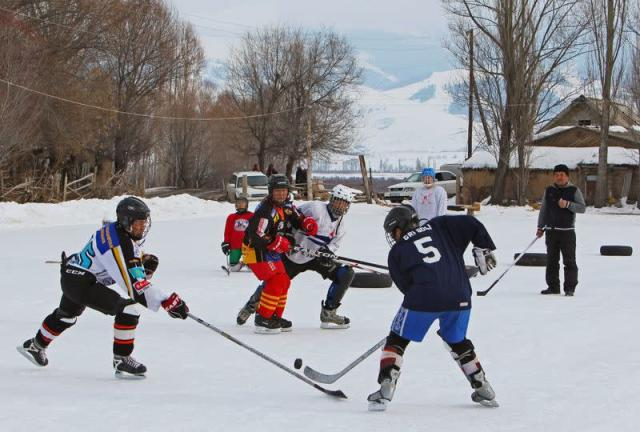 Young hockey players are seen in action during a training match between Kyrgyzstan's first female hockey team and the male team of the Karakol lyceum, in the village of Otradnoye