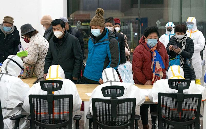 Medical workers help patients infected with coronavirus at a makeshift hospital in Wuhan, central China's Hubei Province.   Xinhua News Agency/Contributor