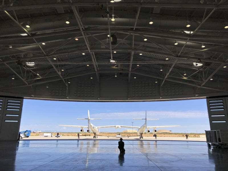 Virgin Galactic ground crew guide the company's carrier plane into the hangar at Spaceport America following a test flight over the desert near Upham, New Mexico, on Thursday, Aug. 15, 2019. The carrier plane is now permanently based at the spaceport after arriving earlier this week. (AP Photo/Susan Montoya Bryan)