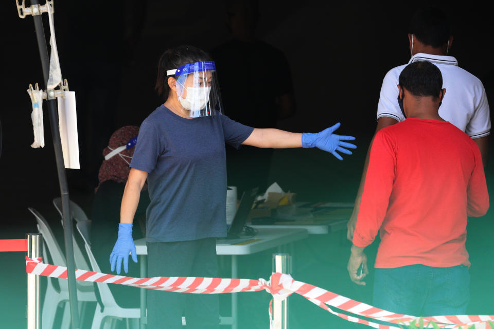 An officer wearing gloves, face shield and protective mask directs the migrant workers in queue to enter a Regional Screening Centre to undergo Rostered Routine Testing (RRT) swab on October 9, 2021 in Singapore. RRT is a surveillance training program for targetted groups who are vulnerable and have higher risk of exposure to COVID-19 which involves recurrent swab testing every 14 days. (Photo by Suhaimi Abdullah/NurPhoto via Getty Images)