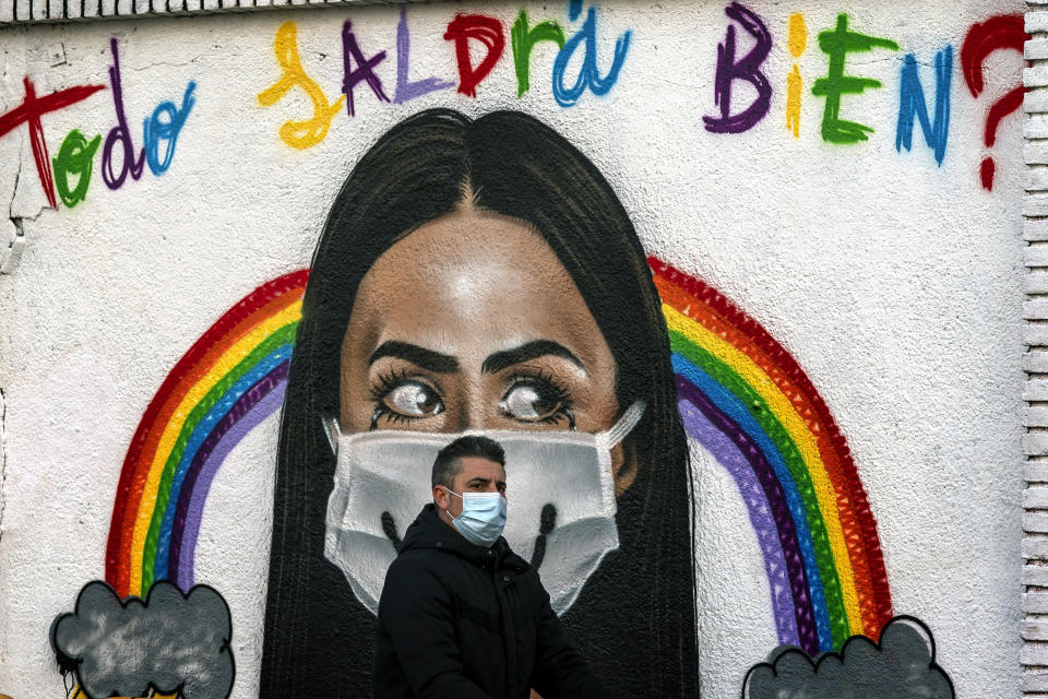 """A man wearing a face mask walks past a graffiti reading in Spanish """"Everything will be alright?"""" in Barcelona, Spain, Tuesday, Jan. 26, 2021. With nearly 2.5 million infections and 55,400 deaths for COVID-19 since the beginning of the pandemic, Spain ranks among the worst-hit countries by the coronavirus in Europe. (AP Photo/Emilio Morenatti)"""