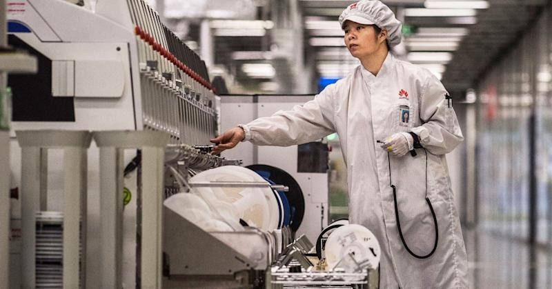 A worker packs up new smartphone devices at the end of the production line at Huawei's production campus on April 11, 2019 in Dongguan, China.
