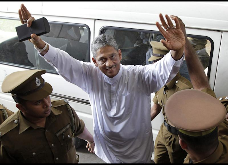FILE - In this Dec. 16, 2011 file photo, defeated presidential candidate and former army chief Sarath Fonseka gestures as he is escorted by prison guards to a court room in Colombo, Sri Lanka. High Court granted bail for Fonseka on Friday, May 18, 2012, a move seen as a step toward a full pardon for the man credited with ending the country's long civil war but who later was jailed after challenging the president in elections. (AP Photo/Gemunu Amarasinghe, File)