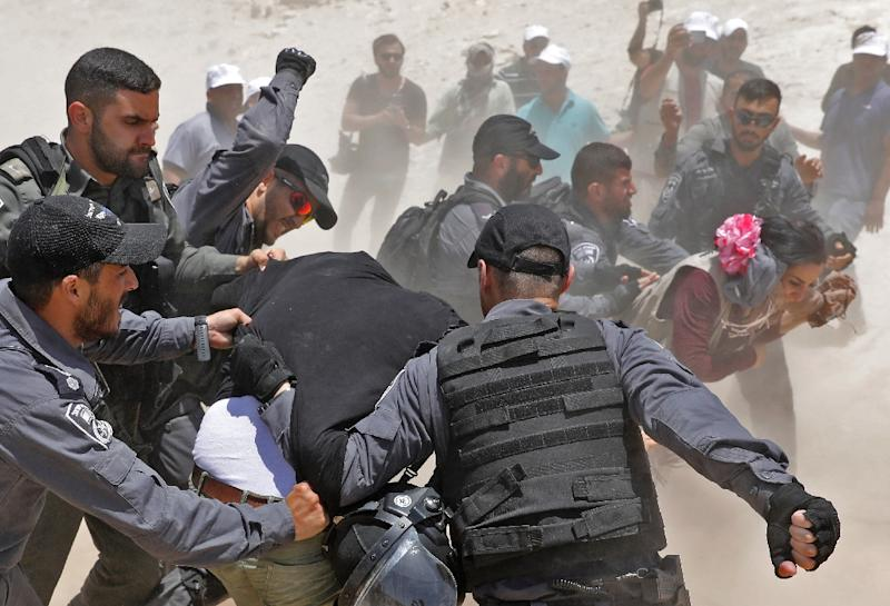 Israeli police scuffle with demonstrators in the Palestinian Bedouin village of Khan al-Ahmar in the occupied West Bank on July 4, 2018 (AFP Photo/Ahmad GHARABLI)