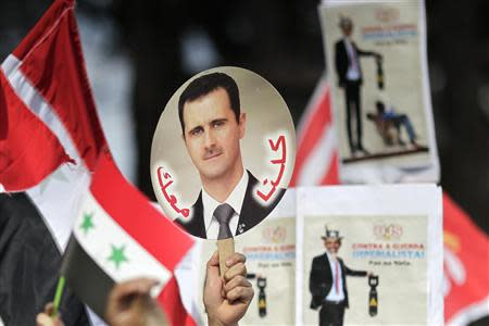 A student holds a sign with a picture of Syria's President Bashar al-Assad during a protest by a students' national union against possible U.S. military action in Syria, in Brasilia