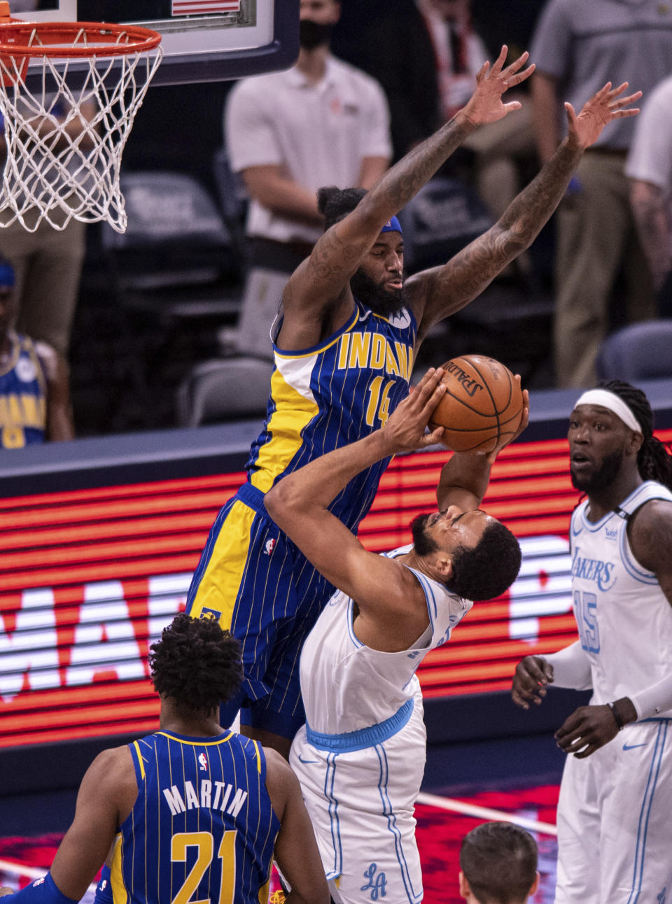 Indiana Pacers forward JaKarr Sampson (14) goes up over the top of Los Angeles Lakers guard Talen Horton-Tucker (5) to block a shot during the second half of an NBA basketball game in Indianapolis, Saturday, May 15, 2021. (AP Photo/Doug McSchooler)