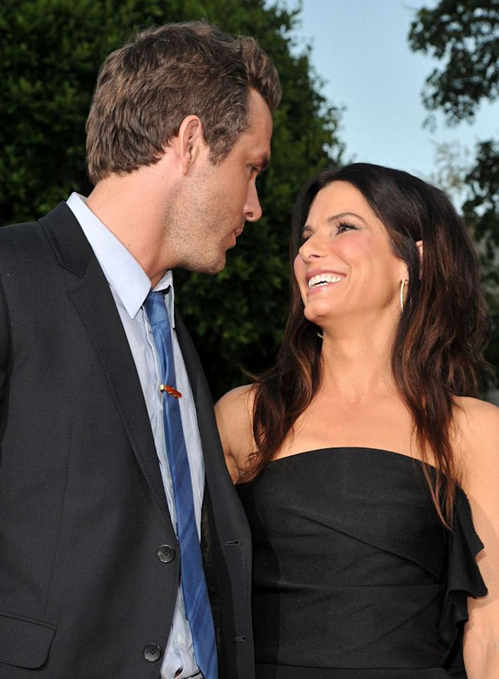 """Sandra Bullock and Ryan Reynolds are now """"shacking up,"""" reports <i>In Touch</i>. The magazine reveals that Reynolds is """"living with Sandra at her LA and Austin, Texas, pads,"""" and has moved his """"clothes and personal belongings, like his computer and photographs, into her place."""" For how happy they are to now live together, and what their next step is, check out what a Bullock confidante leaks to <a href=""""http://www.gossipcop.com/sandra-bullock-ryan-reynolds-living-together-house-moving-home-austin-los-angeles/"""" target=""""new"""">Gossip Cop</a>. Lester Cohen/<a href=""""http://www.wireimage.com"""" target=""""new"""">WireImage.com</a> - August 1, 2011"""