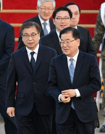 Chung Eui-yong, head of the presidential National Security Office, Suh Hoon, the chief of the South's National Intelligence Service, and other delegates (not pictured) arrive at a military airport in Seongnam, South Korea, March 6, 2018. REUTERS/Song Kyung-Seok/Pool