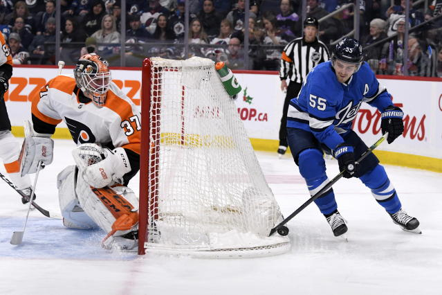 Winnipeg Jets' Mark Scheifele (55) skates around the net as Philadelphia Flyers' goaltender Brian Elliott (37) wayches him during second-period NHL hockey game action in Winnipeg, Manitoba, Sunday, Dec. 15, 2019. (Fred Greenslade/The Canadian Press via AP)