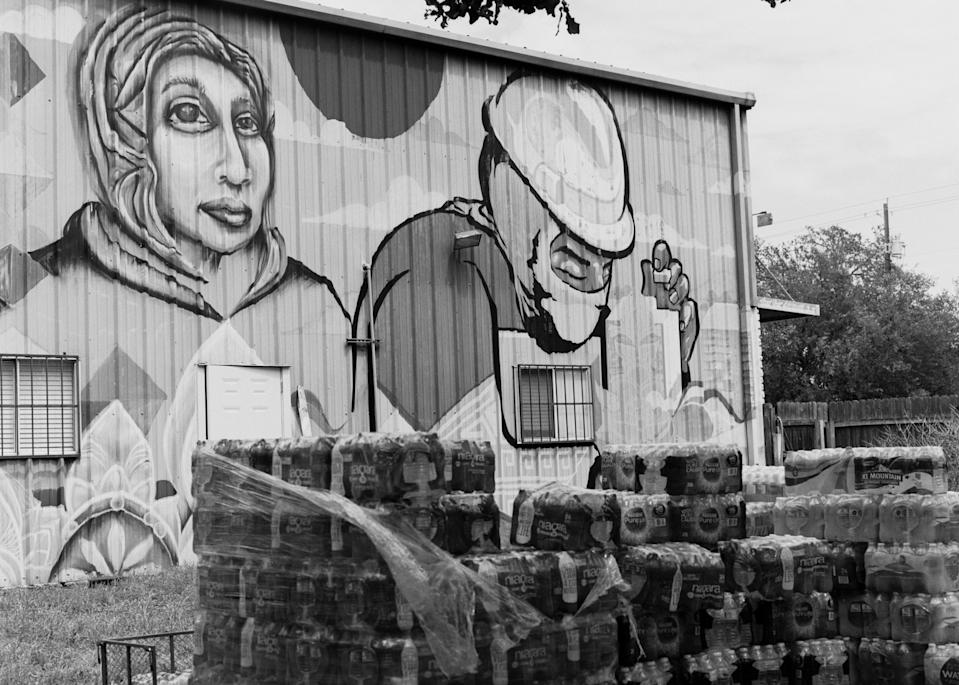 Water bottles stacked outside of the Workers Defense Project headquarters in Austin, Texas, with a mural by Trust Your Struggle Collective. At the beginning of March, 390,000 Texans were still under boil-water advisories after the winter storm.
