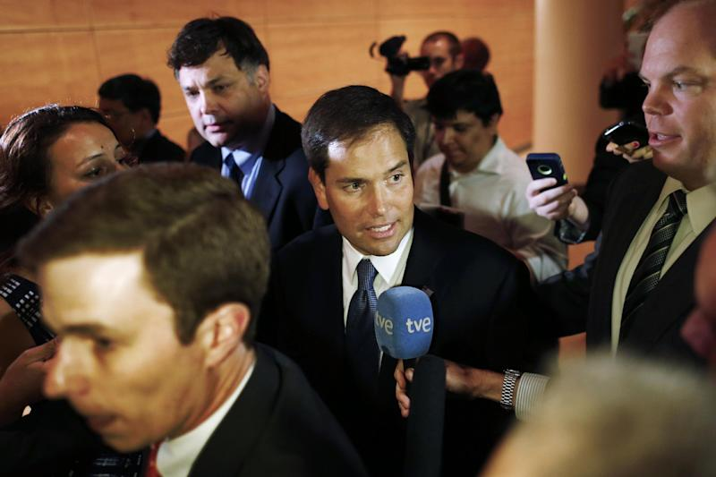 FILE - In this June 13, 2013, file photo Sen. Marco Rubio, R-Fla., center, is pursued by reporters as he leaves after speaking at the Faith and Freedom Coalition Road to Majority Conference in Washington. Rubio spoke last week in July to about 50 conservative activists and other lawmakers at a meeting of the Senate's tea party caucus. Organizers said he breezed past immigration, instead devoting much of his speech to one of the movement's core causes: repealing Obama's health care law. (AP Photo/Charles Dharapak, File)