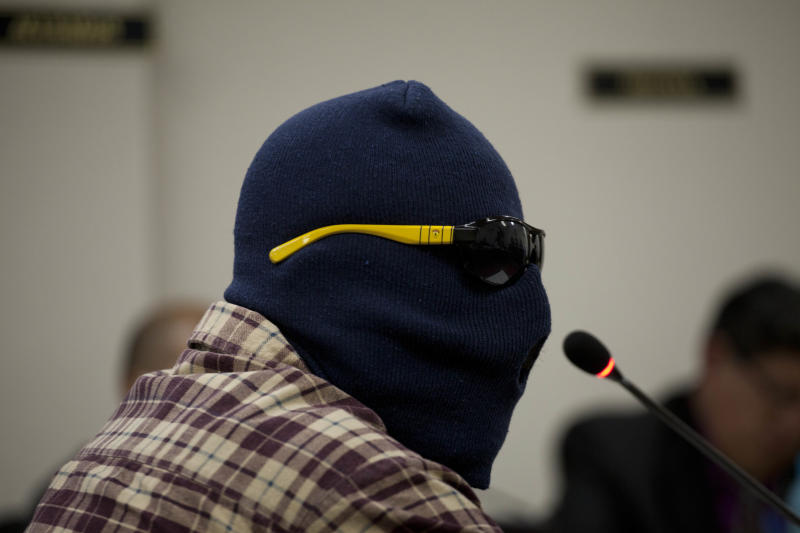 A witness, wearing a ski mask and dark sunglasses to protect his identity, testifies during the El Aguacate Massacre trial in Chimaltenango, Guatemala, Thursday, March 13, 2014. In November 1988 in the mountainous area of western Guatemala, 22 men who lived in the village of El Aguacate where massacred by leftists guerillas during the Guatemalan civil war. The trial that began Thursday, is the first against an ex-guerrilla, who is charged with taking part in the massacre. (AP Photo/Moises Castillo)
