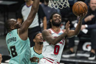 Chicago Bulls guard Coby White (0) tries to shoot while guarded by Charlotte Hornets center Bismack Biyombo (8) during the second half of an NBA basketball game in Charlotte, N.C., Friday, Jan. 22, 2021. (AP Photo/Jacob Kupferman)