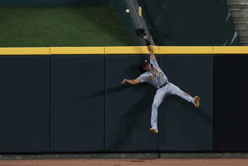 Pittsburgh Pirates' Cole Tucker crashes into the wall as he is unable to make the catch on the three-run home run by Cincinnati Reds' Nicholas Castellanos (2) in the seventh inning during a baseball game at in Cincinnati, Friday, Aug. 14, 2020. (AP Photo/Aaron Doster)