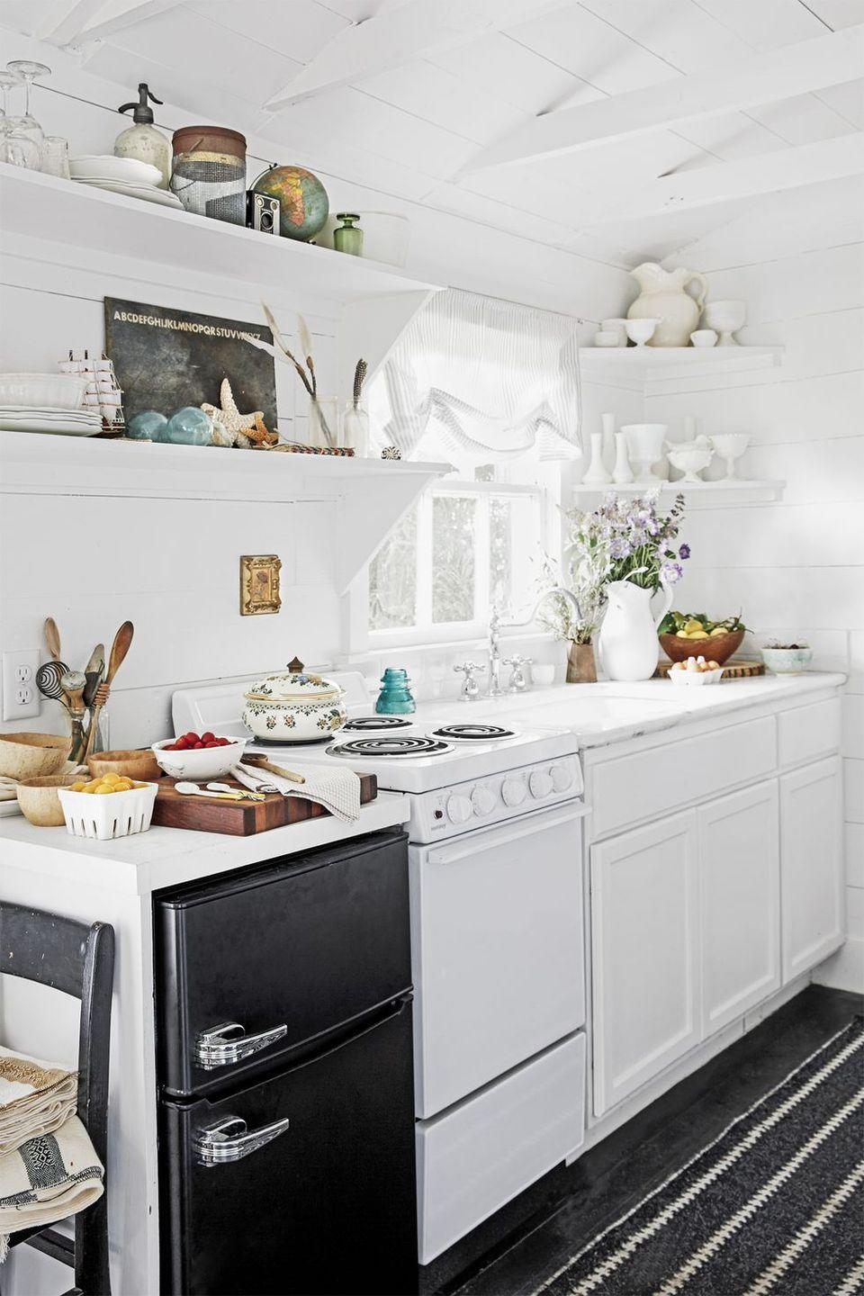 """<p>By sticking to a black-and-white color scheme, Paige makes her modestly sized kitchen appear much larger than it really is.</p><p><a class=""""link rapid-noclick-resp"""" href=""""https://www.amazon.com/Life-Changing-Magic-Tidying-Decluttering-Organizing/dp/1607747308?tag=syn-yahoo-20&ascsubtag=%5Bartid%7C10050.g.1887%5Bsrc%7Cyahoo-us"""" rel=""""nofollow noopener"""" target=""""_blank"""" data-ylk=""""slk:SHOP TIDYING BOOKS"""">SHOP TIDYING BOOKS</a></p>"""